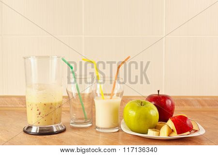 Fresh apples and a glasses of milk shake on kitchen table