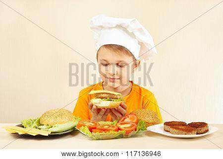 Little smiling boy in chefs hat preparing hamburger