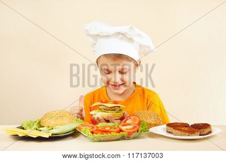 Little funny chef in chefs hat preparing hamburger