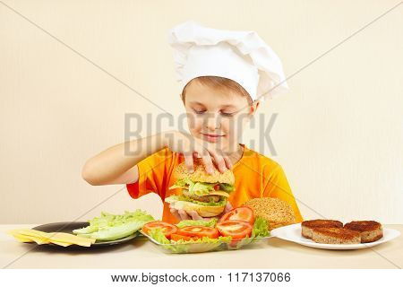 Young smiling chef shows how to cook hamburger