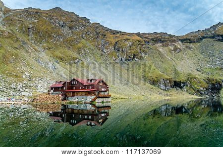 BALEA CHALET, ROMANIA - SEPTEMBER 19 2015: view of Balea Lake cottage on Fagaras Mountains, Romanians Carpathians. The image of the chalet is reflected in the lake.