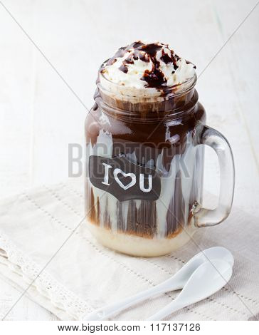 Iced cold coffee, frapuccino with whipped cream and chocolate syrup in jar with chalkboard I Love Yo