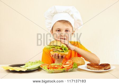 Young funny boy in chefs hat enjoys cooking tasty hamburger