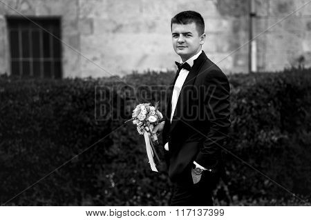 Handsome Wealthy Stylish Groom In Suit With Bouquet Outdoors B&w