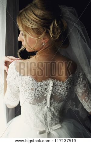 Beautiful Blonde Wedding Bride In Make-up And Veil In A White Dress Back Close-up