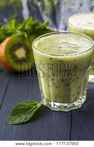 Two glasses of homemade smoothie with kiwi banana and mint leaves .