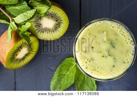 Glass of homemade smoothie with kiwi banana and mint leaves .