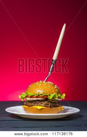 Hamburger with vegetables on white plate with fork on wooden table.