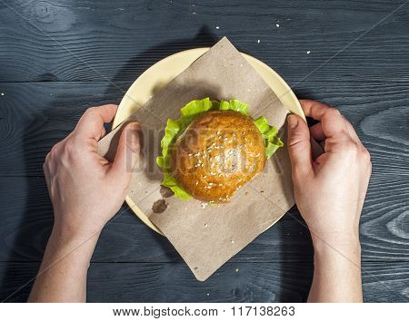 Appetizing hamburger with vegetables on white plate with fork and knife on wooden table.