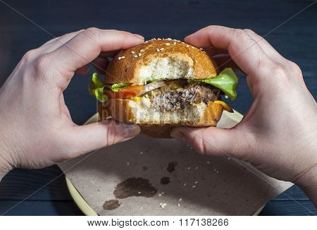 Hamburger with vegetables in woman's hands