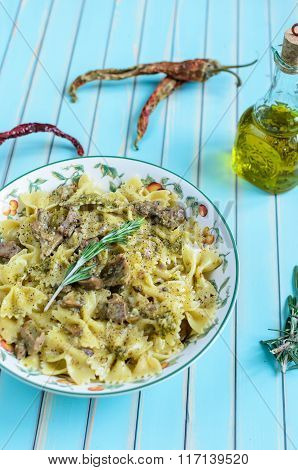 Pasta Farfalle With Turkey, Pesto Sauce And Rosemary In Serving Plate Over Wooden Turquoise Backgrou
