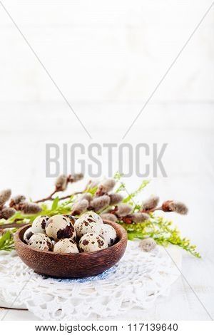 Quail eggs in a wooden bowl Easter white background Willow and green spring branch with leaves Copy