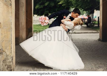 Happy Handsome Groom And Blonde Beautiful Bride In White Dress Kissing Under Arc