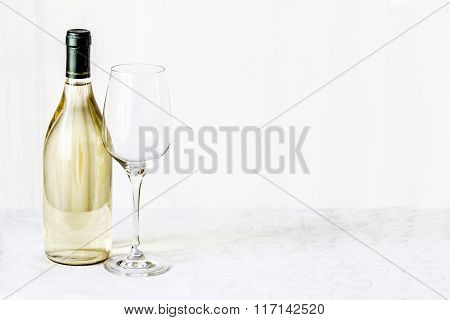 Bottle Of Wine And Empty Wineglass Are Stand On The White Tablecloth