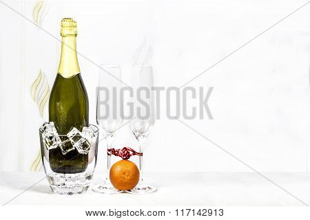 Bottle Of Champagne In Ice Bucket And Two Empty Glasses With Mandarin Are Standing On A White Tablec