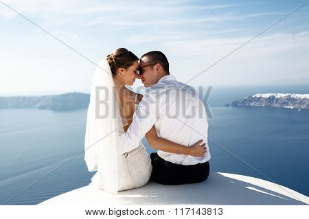 Happy Married Couple Kissing On Terrace With Sea And Mountains Background, Santorini