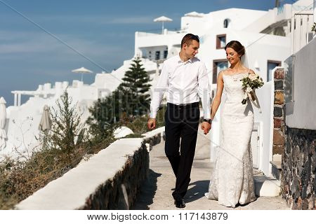 Groom And Bride With Bouquet Walking On Stairs And Holding Hands Town Background