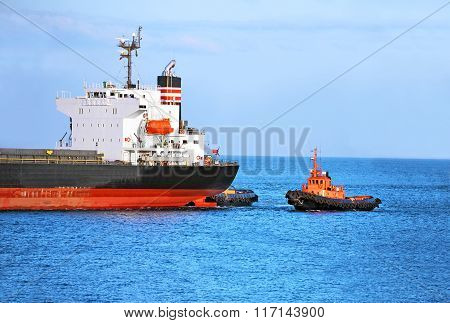 Tugboat assisting cargo ship