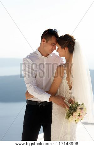 Handsome Happy Groom And Bride In White Dress Hugging Sea And Islands Background
