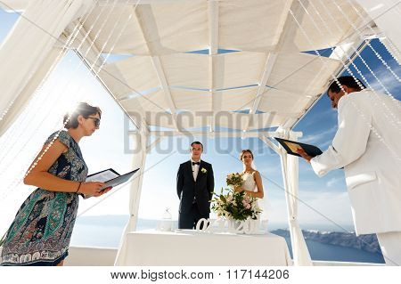 Happy Groom And Bride At Wedding Aisle During Ceremony With Sea In Background