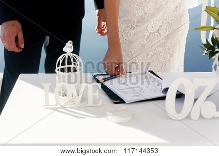Happy Bride Signing Wedding Certificate On White Table Closeup, Santorini