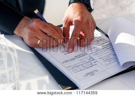 Happy Groom Signing Wedding Certificate On White Table Closeup, Santorini