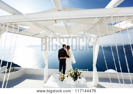 Newlywed Husband And Wife Hugging At Terrace Looking At Sea In Santorini