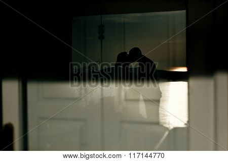 Silhouette On The Wall Of Newlywed Man And Woman Kissing Closeup