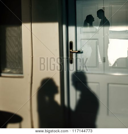 Silhouette On The Wall Of Newlywed Man And Woman Hugging Closeup