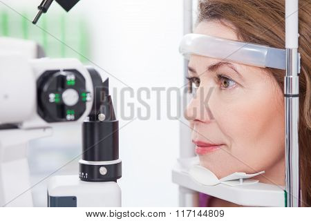 Mature lady is looking into eye test machine