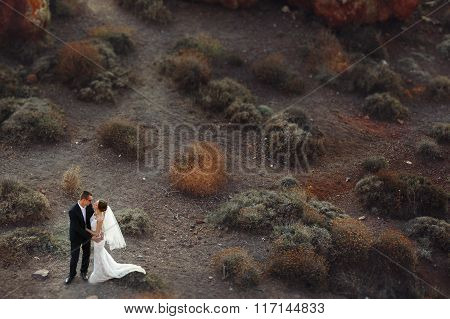 Married Couple, Bride And Groom, Posing On Mountain Volcano Landcape In Santorini, Greece