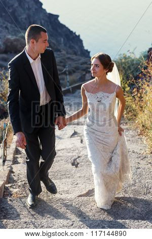 Happy Bride And Groom Holding Hands And Walking On Stairs In Mountains