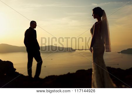 Married Couple Bride And Groom Posing At Sunset In The Mountains, Santorini, Greece