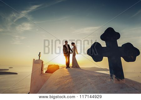 Handsome Groom And Beautiful Bride Posing On Church Roof At Sunset Sky Background