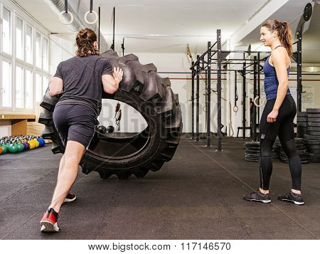 Couple Working Out With Tire At Cross fit Gym