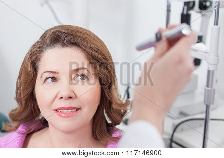 Experienced oculist is examining eyes of patient