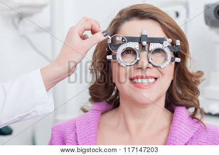 Cheerful female optician is examining human eyes