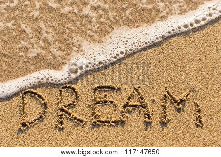 Dream - inscription on sand beach with the soft wave.