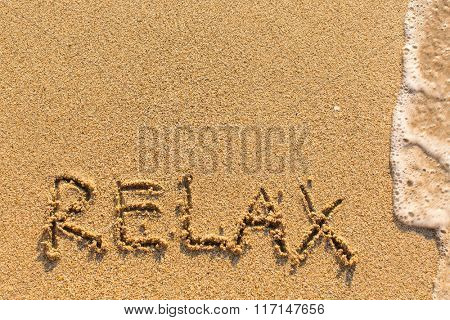 Relax - word drawn on the sand beach with the soft wave.