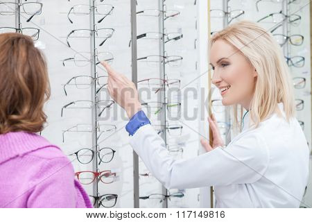 Cheerful female optometrist is consulting mature lady