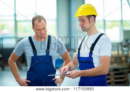 Two Worker In Factory Using Tablet Pc