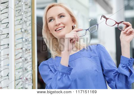 Pretty blond girl is choosing glasses in store