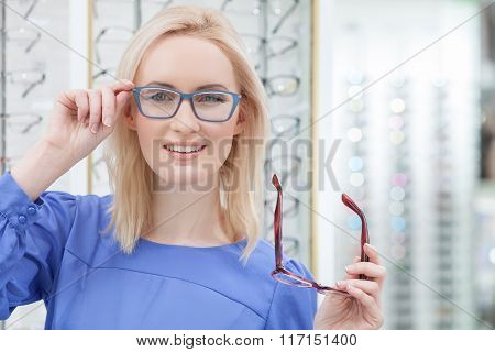 Attractive young woman is wearing spectacles in shop