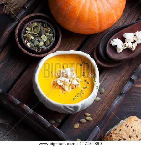 Pumpkin soup with salty popcorn in a white ceramic bowl with fresh pumpkin on a wooden background To