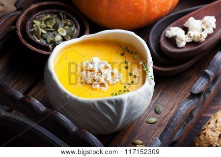 Pumpkin soup with salty popcorn in a white ceramic bowl with fresh pumpkin on a wooden background