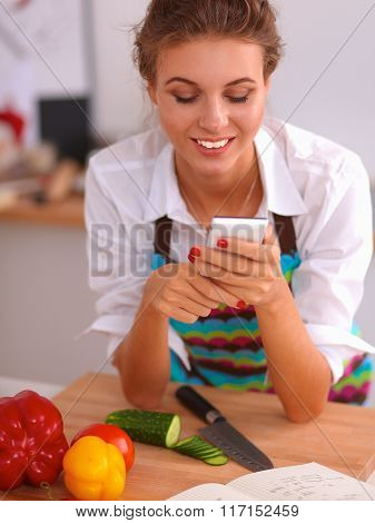 Smiling woman holding her cellphone in the kitchen