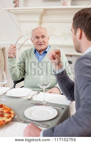 Cheerful two men on family dinner