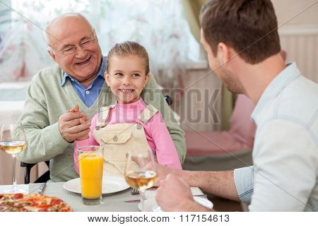 Cheerful mature grandfather is dining with his children