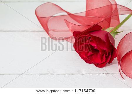 Single Red Rose With Organza Red Ribbon On White Wood Background