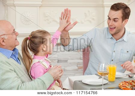 Cheerful old man is dining with his children